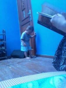 Ini foto yang diambil oleh anak pertamaku. Aku tidak tahu ia memfoto adiknya, dan secara tidak sengaja turut memfoto (tangan) aku yang sedang membaca buku. Waktu itu aku lagi santai-santai membaca buku sambil membiarkan anak-anakku bermain apa pun yang sedang ingin mereka lakukan di dalam kamar.